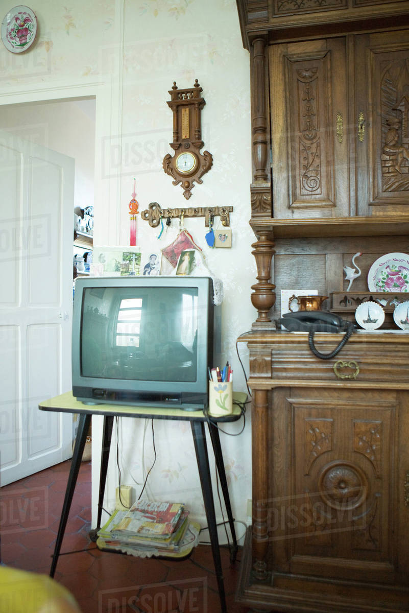 TV next to china cabinet in living room stock photo
