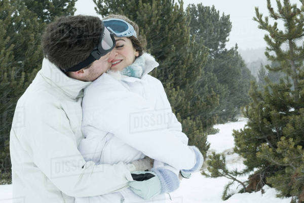 Young couple dressed in ski clothes kissing Royalty-free stock photo