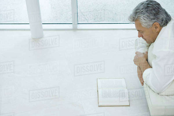 Mature man lying on stomach reading book, cropped view Royalty-free stock photo