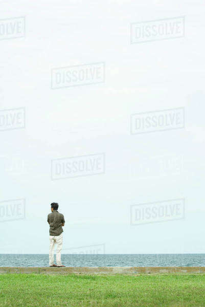 Man standing, looking out toward sea, full length, rear view Royalty-free stock photo