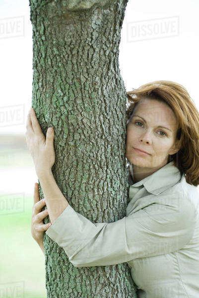 444a6ec8120cd7 Woman hugging tree trunk