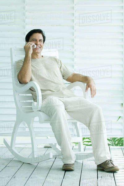 Man sitting in rocking chair, using cell phone, full length Royalty-free stock photo