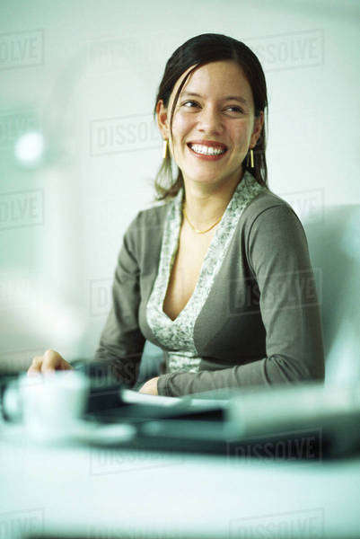 Woman sitting at desk, smiling, looking away Royalty-free stock photo