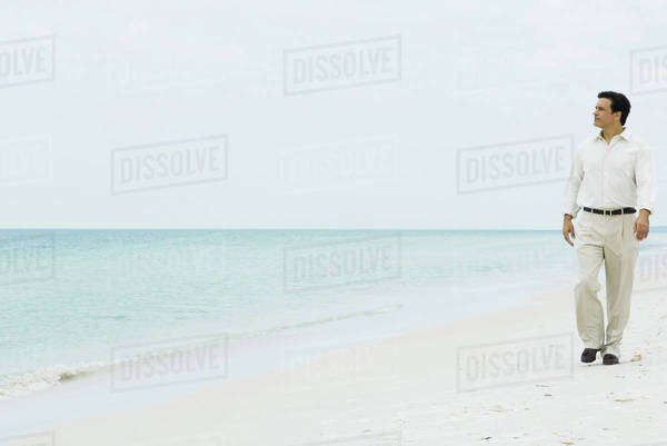 Man walking across beach, looking at distance, full length, front view Royalty-free stock photo