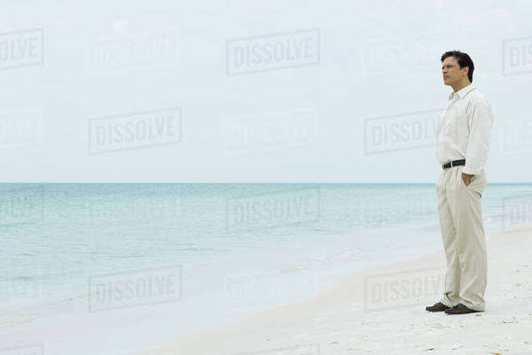 Man standing on beach, looking at view Royalty-free stock photo
