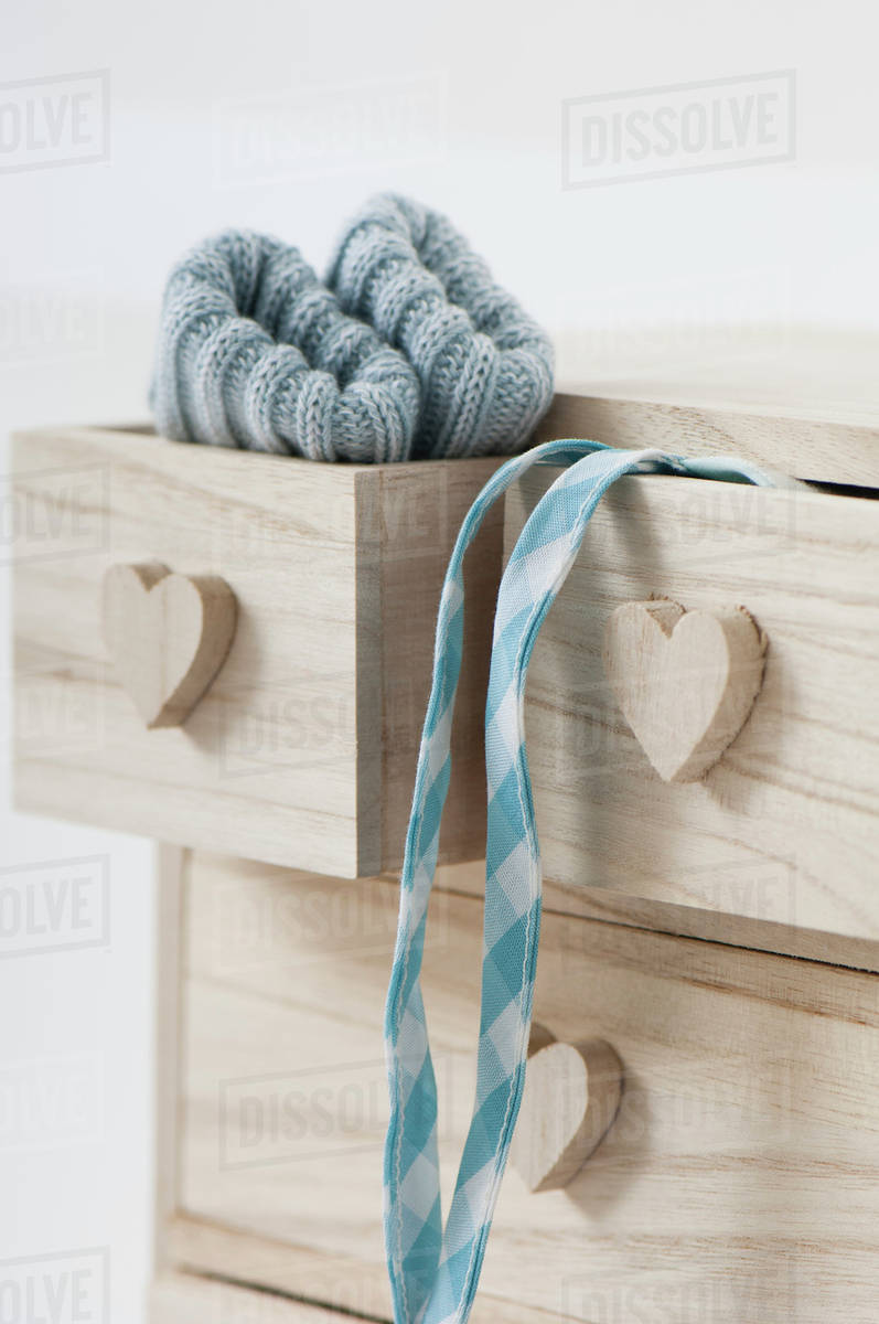 Clothing Hanging Out Of Wooden Drawers With Heart Shaped Knobs
