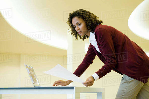 Businesswoman using laptop computer and looking at document Royalty-free stock photo