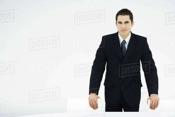 Businessman leaning on backs of chairs, looking at camera Royalty-free stock photo