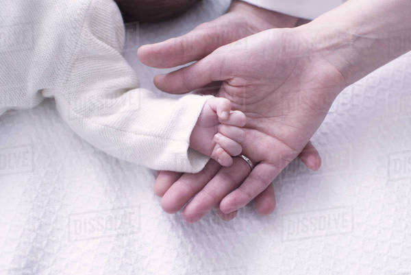 Close-up of baby's hand resting on parents' hands Royalty-free stock photo