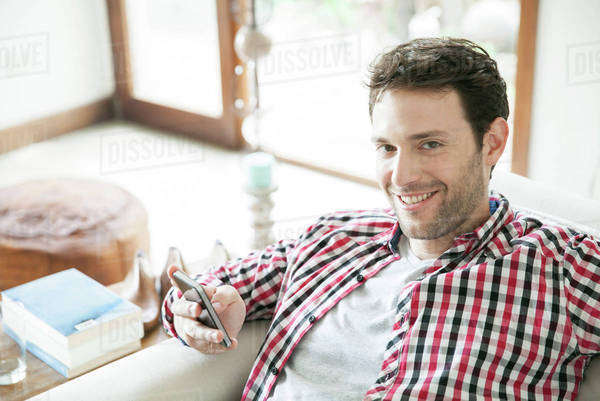 Man using smartphone at home, smiling Royalty-free stock photo