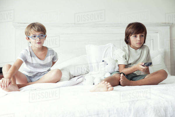 Boys watching tv on bed, portrait Royalty-free stock photo