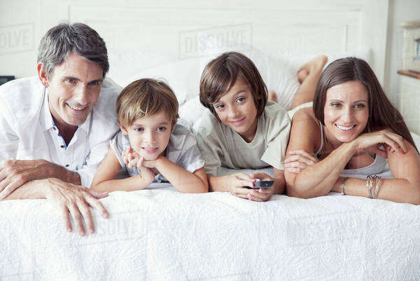 Family watching TV on bed, portrait Royalty-free stock photo