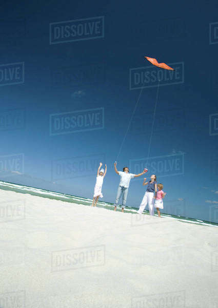 Family flying kite on beach Royalty-free stock photo