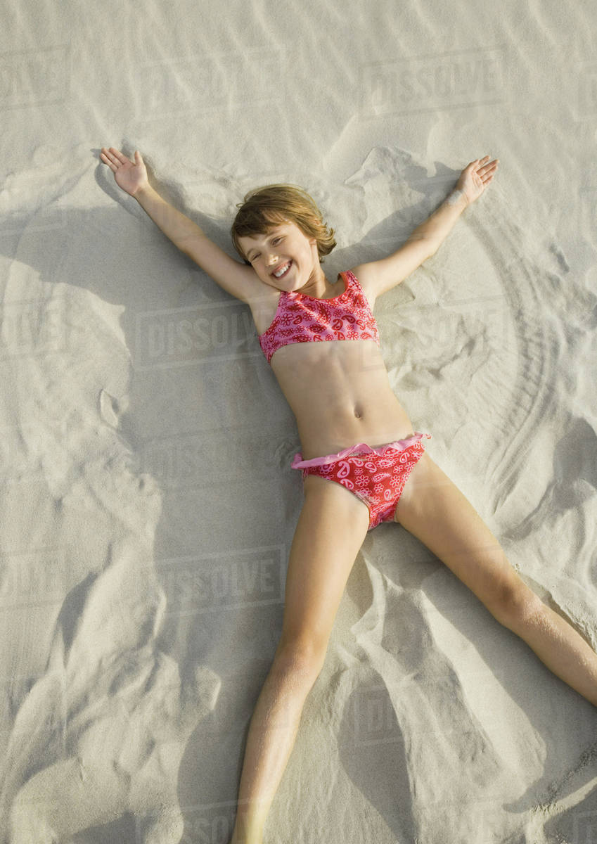 Girl Making Angel In Sand On Beach High Angle View