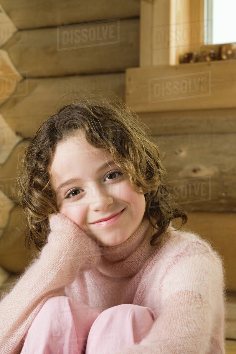 Girl Sitting With Knees Up Smiling At Camera Stock Photo Dissolve