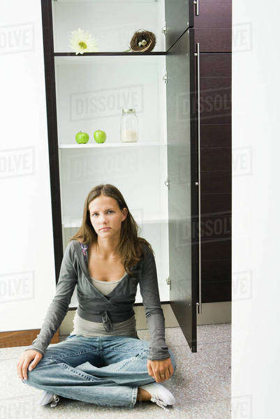 Teenage girl sitting on floor in front of sparse pantry Royalty-free stock photo