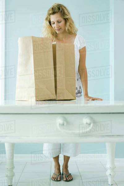 Woman looking into grocery bag Royalty-free stock photo
