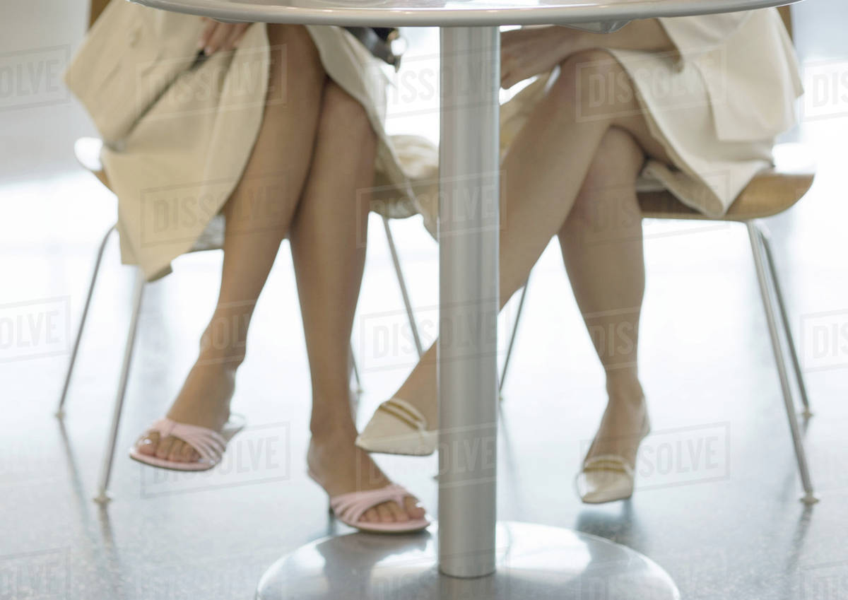 Two women sitting at table view of legs under table Stock Photo