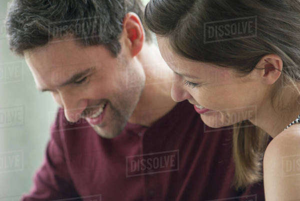 Couple relaxing together, both looking down and smiling Royalty-free stock photo