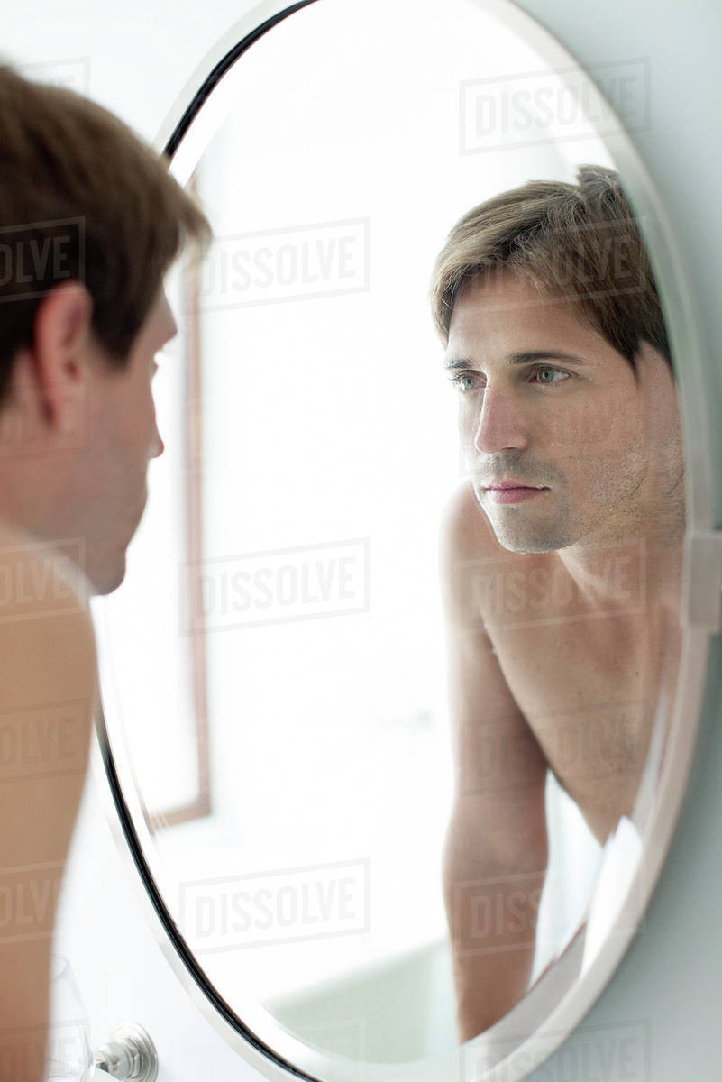 man looking at self in mirror stock photo dissolve