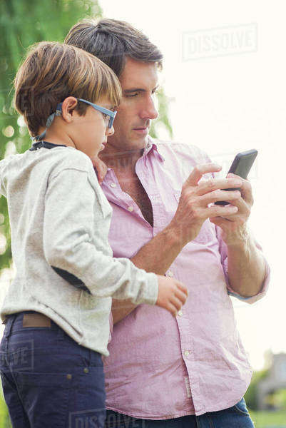 Father and young son looking at smartphone together outdoors Royalty-free stock photo