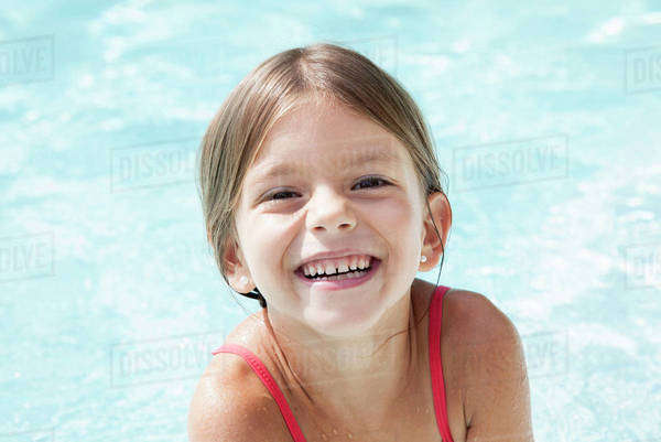 Little girl in pool, smiling cheerfully, portrait Royalty-free stock photo