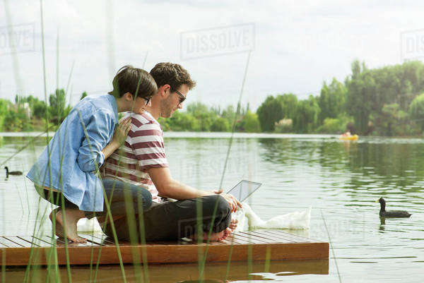 Couple using laptop computer on dock Royalty-free stock photo