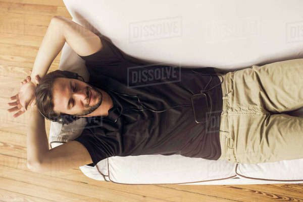 Man reclining on couch listening to music playing on smartphone Royalty-free stock photo