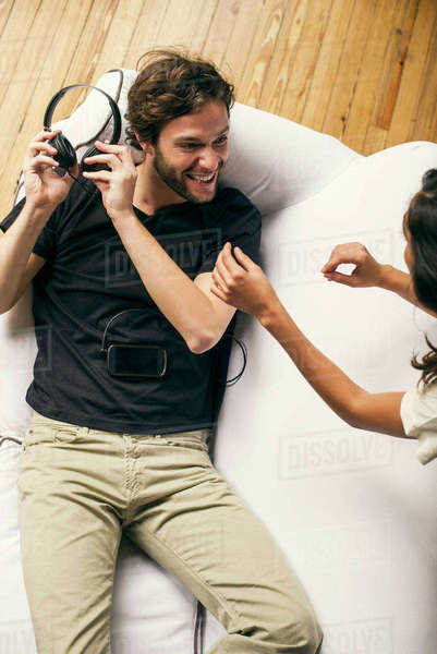 Man playfully withholding headphones from girlfriend Royalty-free stock photo