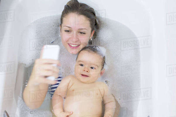 Mother using smartphone to photograph herself and baby while taking a bath Royalty-free stock photo