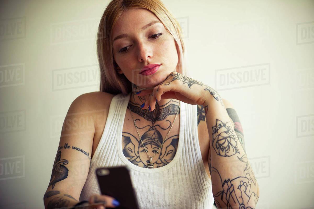 Tattooed woman using smartphone Royalty-free stock photo