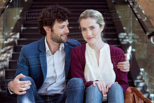 Happy couple sitting together on stairs Royalty-free stock photo