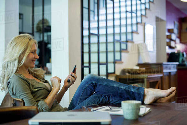 Woman relaxing at home with smartphone Royalty-free stock photo