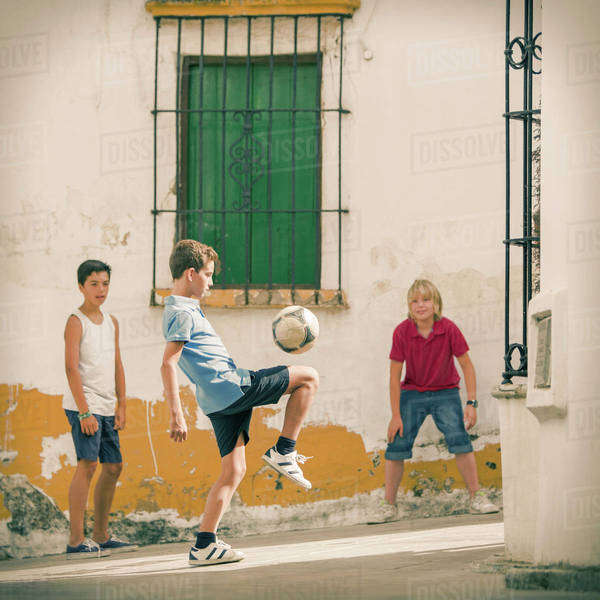 Children playing with soccer ball in alley Royalty-free stock photo