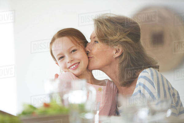 Older woman kissing granddaughter at table Royalty-free stock photo