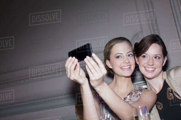 Smiling women taking self-portrait with camera phone Royalty-free stock photo