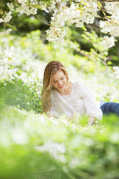 Woman reading book in grass under tree with white blossoms Royalty-free stock photo