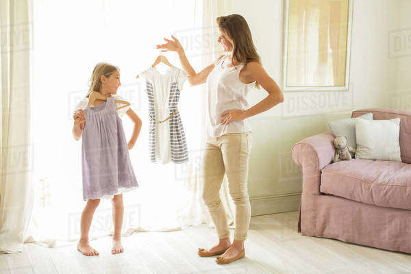 Mother and daughter picking out clothes in bedroom Royalty-free stock photo