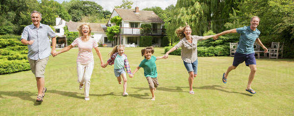 Multi-generation family holding hands and running in grass Royalty-free stock photo