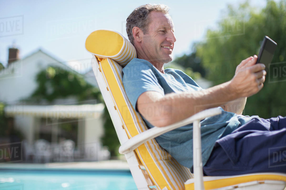 Man Reading In Lounge Chair At Poolside