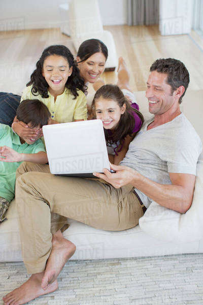 Family using laptop on sofa in living room Royalty-free stock photo