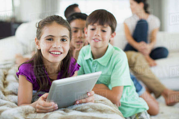 Children using digital tablet on sofa in living room Royalty-free stock photo