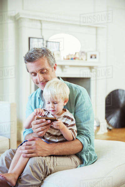 Father and son using cell phone in living room Royalty-free stock photo