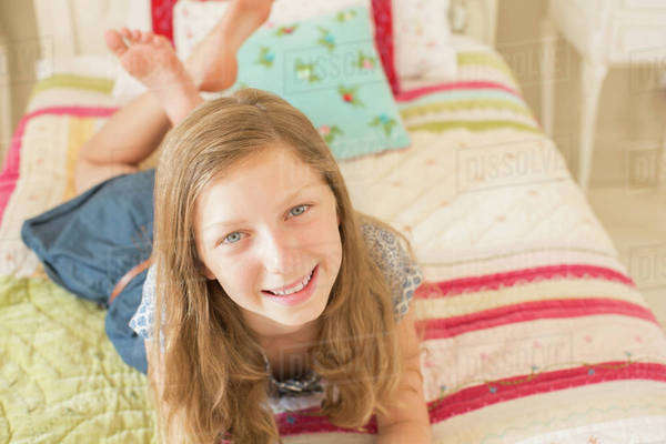 Smiling girl laying on bed Royalty-free stock photo