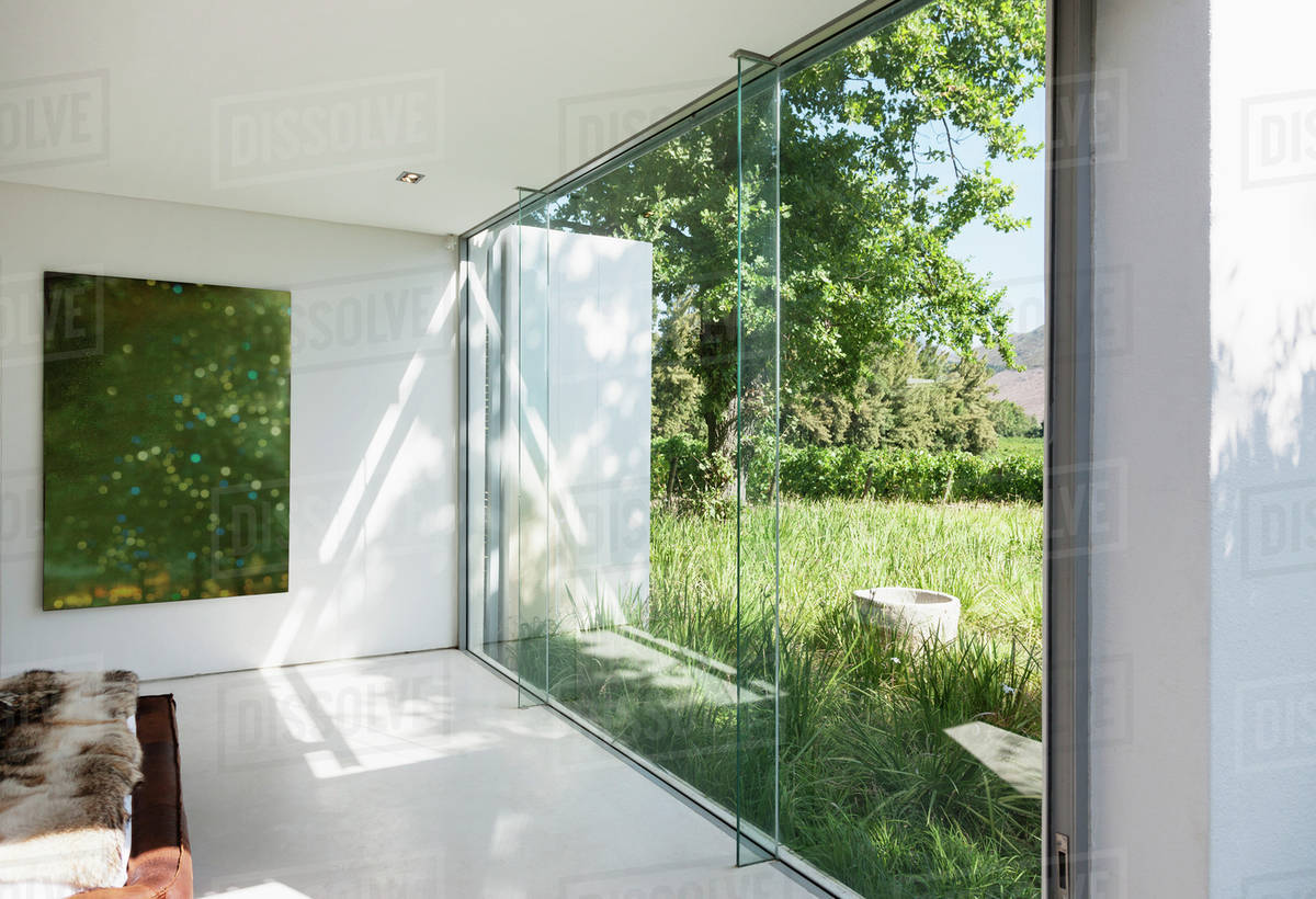 Modern house with glass walls overlooking grass