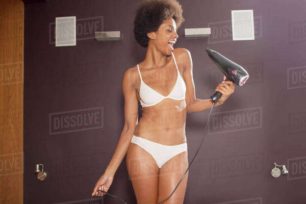 Woman in bra and panties singing into hair dryer in bathroom Royalty-free stock photo