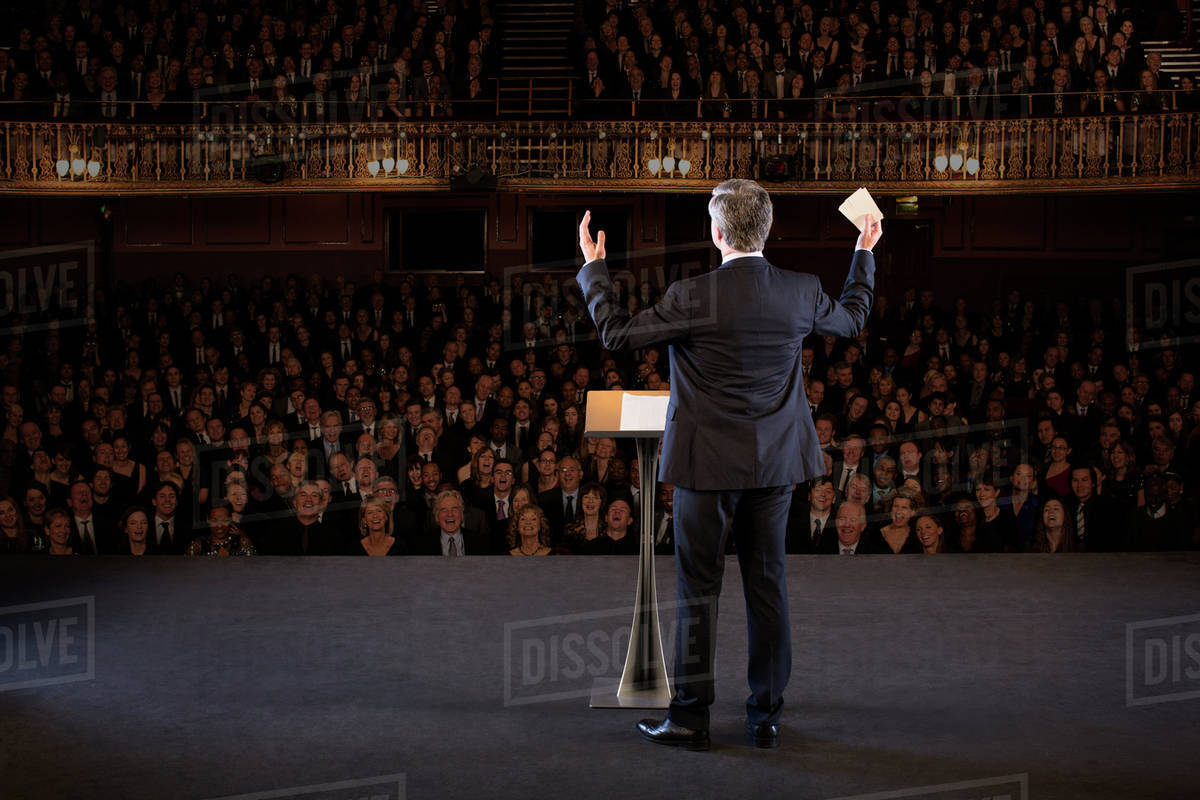 Speaker gesturing on stage in theater Royalty-free stock photo
