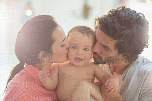 Parents kissing baby boy's cheeks Royalty-free stock photo