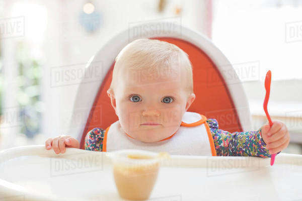 Baby girl eating in high chair Royalty-free stock photo