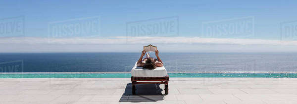 Woman relaxing on lounge chair at poolside overlooking ocean Royalty-free stock photo